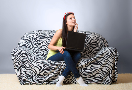 Pretty girl with laptop sitting on the sofa photo