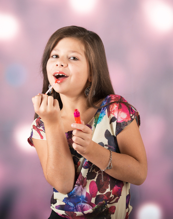Portrait of a beautiful little lady applying lip gloss, abstract background