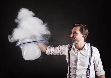 alzando la mano: Artist hold big soap bubble with the smoke in his hands. Bubble show studio concept.