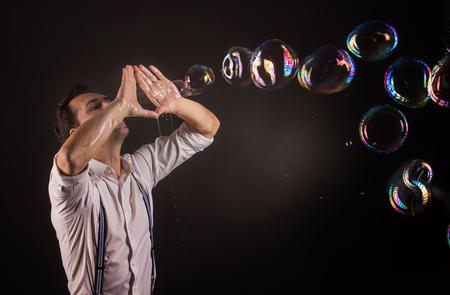 alzando la mano: Artista soplando muchas burbujas de jabón de sus manos. Bubble show estudio concepto.