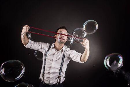 alzando la mano: Artist blowing many soap bubbles from his hands. Bubble show studio concept.