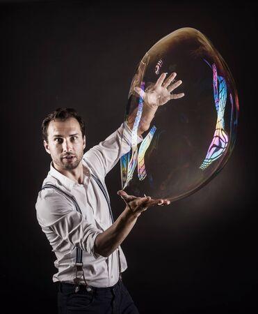 alzando la mano: Artista celebrar gran burbuja de jabón en sus manos. Bubble show estudio concepto.