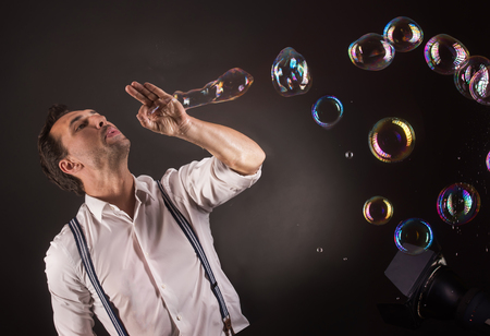 miraculous: Artist blowing many soap bubbles from his hands. Bubble show studio concept.