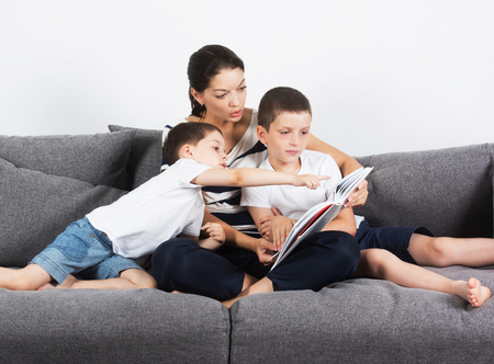 Mother reads an interesting book with her sons of the sofa. Studio portrait on white background. photo