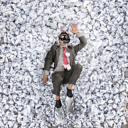 Business man with a great heap of crumpled papers. Swimming in paper ocean concept.