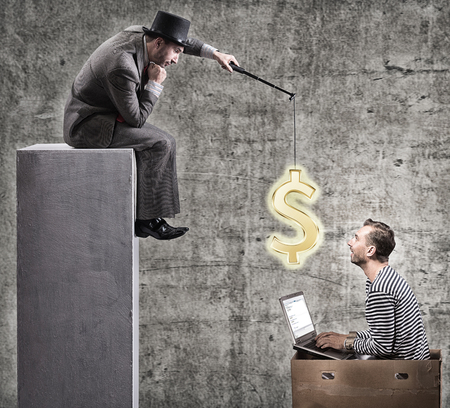 A greedy businessman motivates office workers with a salary. Office slavery concept. Archivio Fotografico