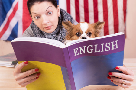 Simple learning language concept. English even for dog. Young woman and her dog learning english language. 版權商用圖片