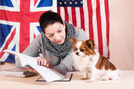 Simple learning language concept. English even for dog. Young woman and her dog learning english language. Foto de archivo