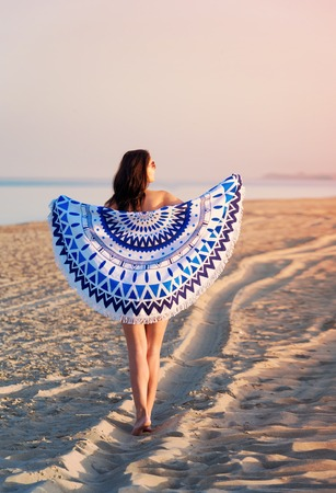 Pretty woman with a mandala round beach tapestry in the ocean coast. Фото со стока
