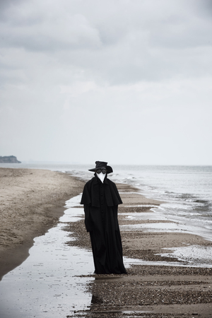 Plague doctor in seaside. Outdoor portrait with dramatic sky in background. 写真素材 - 101791540