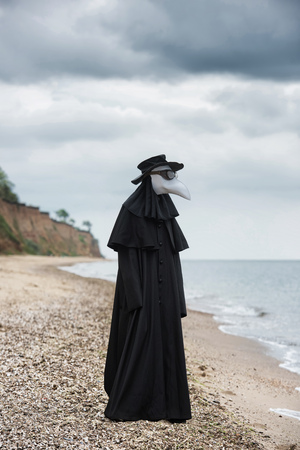 Plague doctor in seaside. Outdoor portrait with dramatic sky in background. 写真素材