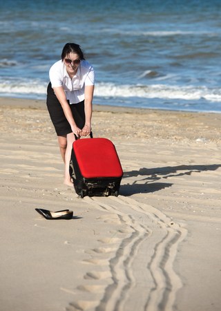 Out of office vacation at sea. Woman drags the suitcase over the sands to the seaside.