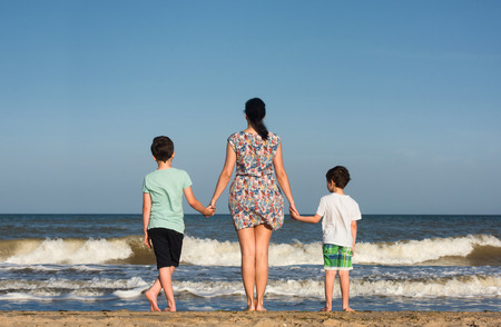 Mother and her sons look at the ocean.