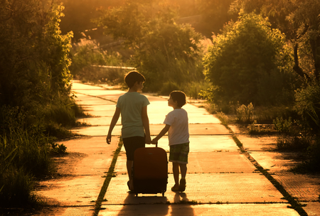 Two brothers on the road with travel bag at sunset.