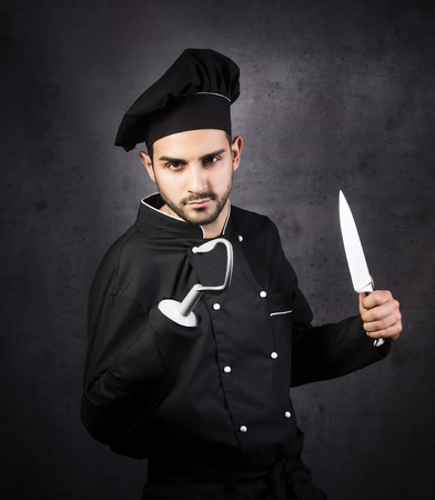 A humorous portrait of a pirate-style chef cooker in black uniform on grey beckground.