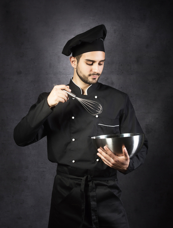 Portrait of a chef cooker in black uniform, gray background