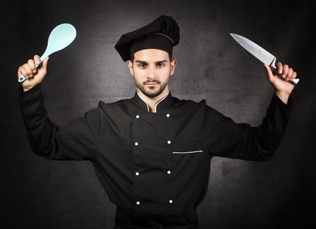 Portrait of a chef cooker with knife and spoon in black uniform, gray background