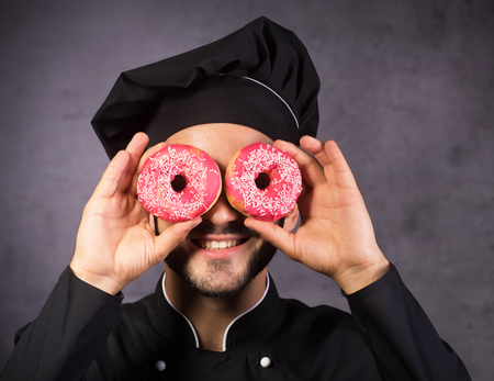 Diet, calories, healthcare, willpower, summer, body care, concept. Close up portrait of happy cute chef cooker with sweet donuts like specs, laughing.
