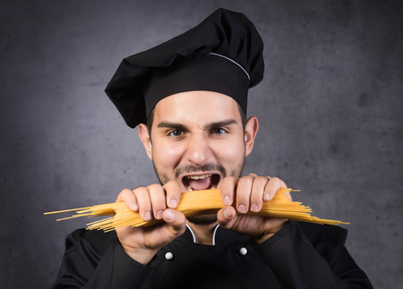 Portrait of a chef cooker in black uniform with spaghetti in his hand, gray background Stock Photo