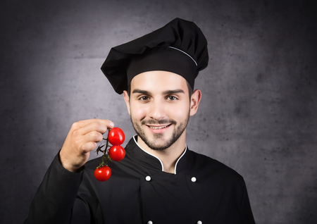 Portrait of a chef cooker in black uniform with tomatos, gray background Stock Photo