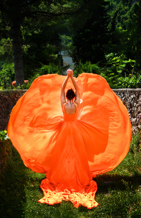 Beautiful girl in amazing fluttering orange dress. Butterfly concept.