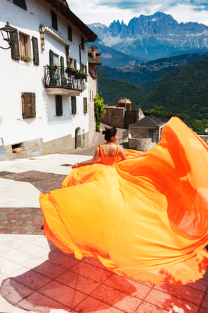 Beautiful girl in amazing fluttering orange dress running forward in old town. With mountais on background. Stock Photo