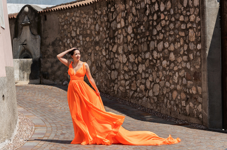 Beautiful girl in amazing fluttering orange dress.