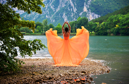 Beautiful girl in amazing fluttering orange dress. With  lagoon and mountains on background.