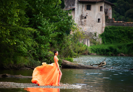 Beautiful girl in amazing fluttering orange dress. With old castel and the lagoon on background.