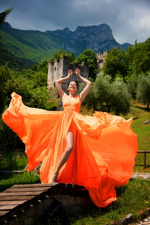 Beautiful girl in amazing fluttering orange dress. With old castel  on background.