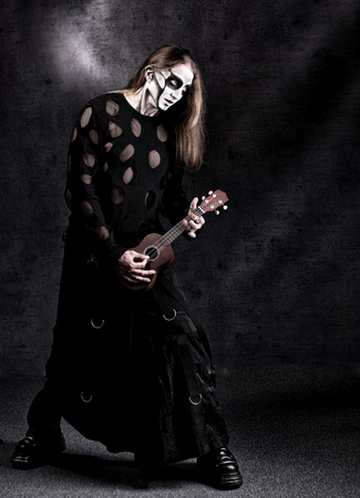 Humorous full length portrait of man in goth style clothes with little guitar in his hand.