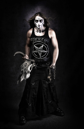 Full length portrait of man in goth style clothes with skull in his hand.
