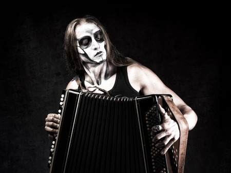 Humorous portrait of man in goth style clothes and skull makeup with the Russian bayan (button accordion).
