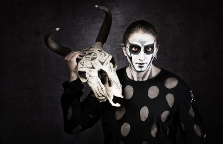 Portrait of man in goth style clothes with skull in his hand. Stock Photo