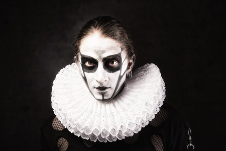 Portrait of man in goth style clothes and  ruff collar with skull makeup.