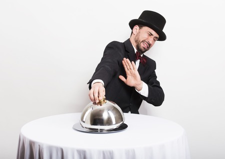 Studio portrait of a funny retro man looking into a silver cloche Stock Photo