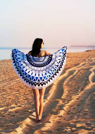 Pretty woman with a mandala round beach tapestry in the ocean coast. Stock Photo