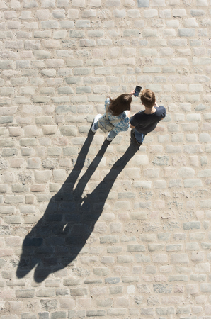 Young boy and girl look at mobile phone n the street. View from above. Stock Photo