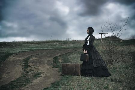 Portrait extérieur d'une dame victorienne en noir assise seule sur la route avec ses bagages.