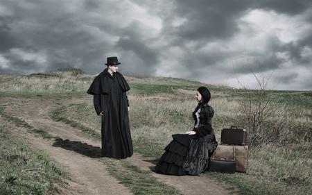 Portrait extérieur d'une dame victorienne en noir assise sur la route avec ses bagages et monsieur debout à proximité.