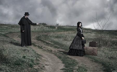 Outdoor-Porträt einer viktorianischen Dame in Schwarz und Gentleman, die mit ihr von den gegenüberliegenden Seiten der Straße spricht. Standard-Bild