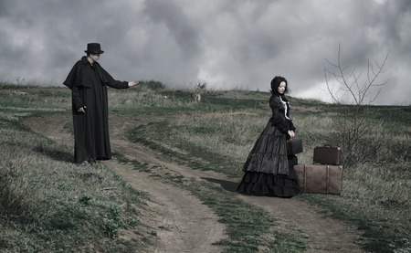 Outdoors portrait of a victorian lady in black and gentleman talking to her from the oppisite sides of the road.