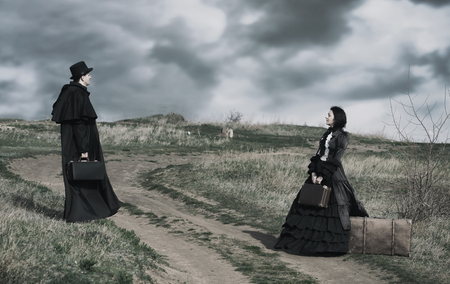 Outdoors portrait of a victorian lady in black and gentleman standing on the oppisite sides of the road.
