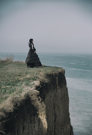 Outdoors portrait of a victorian lady in black standing on the cliff. 写真素材 - 121468258