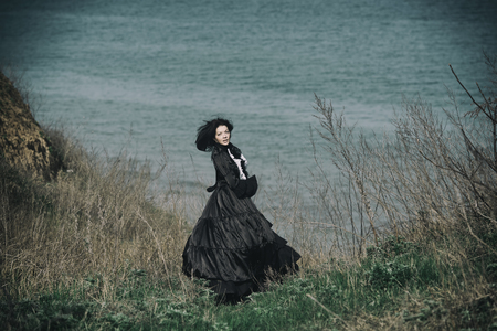 Outdoors portrait of a victorian lady in black. Run away and turned her head.