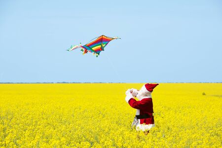 Christmas Santa Claus fling a kite in blooming yellow field. Spring vacation concept. 写真素材