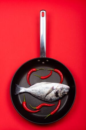 Fresh fish dorado with chilli on a frying pan on a red background. View from above. 写真素材