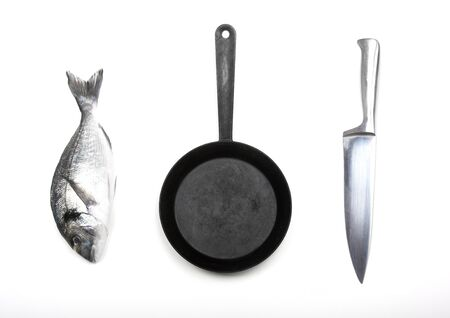 Fresh fish dorado, knife and frying pan on a white background. View from above.
