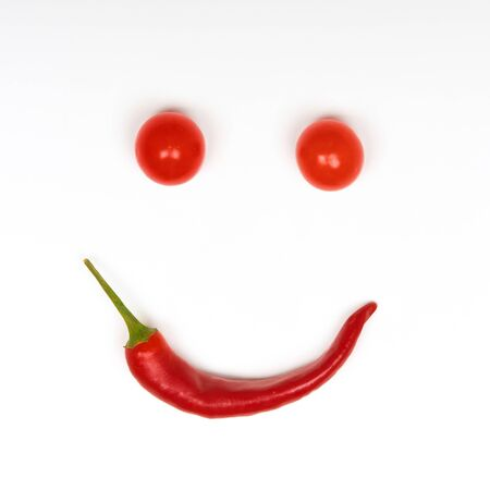 Collage in the form of smiles from tomatoes and chili isolated on a white background 写真素材