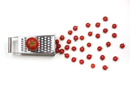 Tomatoe on a grater and cherry tomatoes. One to many separation concept. 写真素材 - 129449978